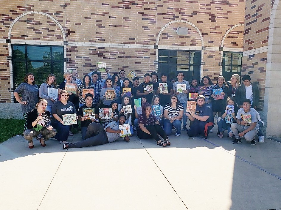 """""""a group of kids pose with books outside of their school"""""""