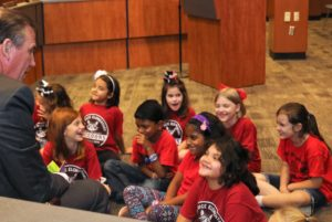 second grade girls sit on the floor of a board room and laugh with a man in a suit who read the story
