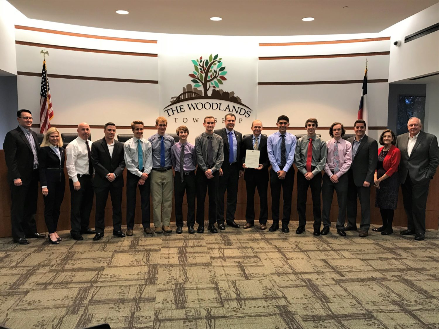 the boys cross country team poses for a picture after winning their third consecutive state championship