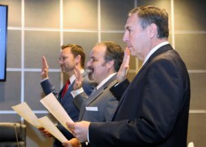 Three men in suits recite an oath.