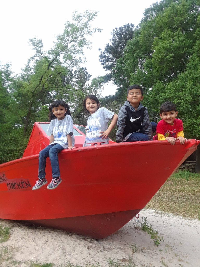"""four students sit on a boat"""