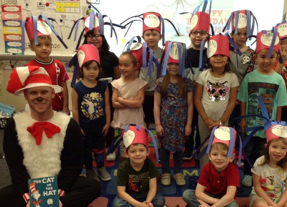 """children in a classroom pose with self created Thing 1 and 2 hats on their heads"""