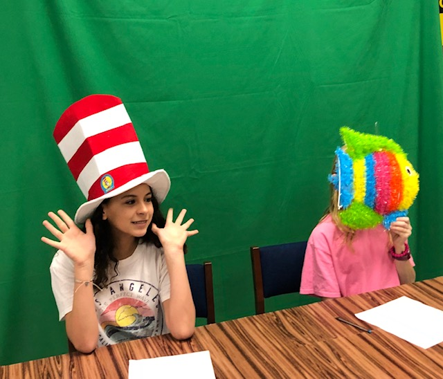 """two students donning Dr. Seuss attire sit at a table"""