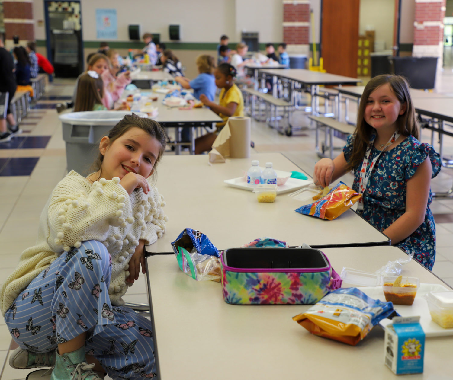 Two students sit together at the lunch table.