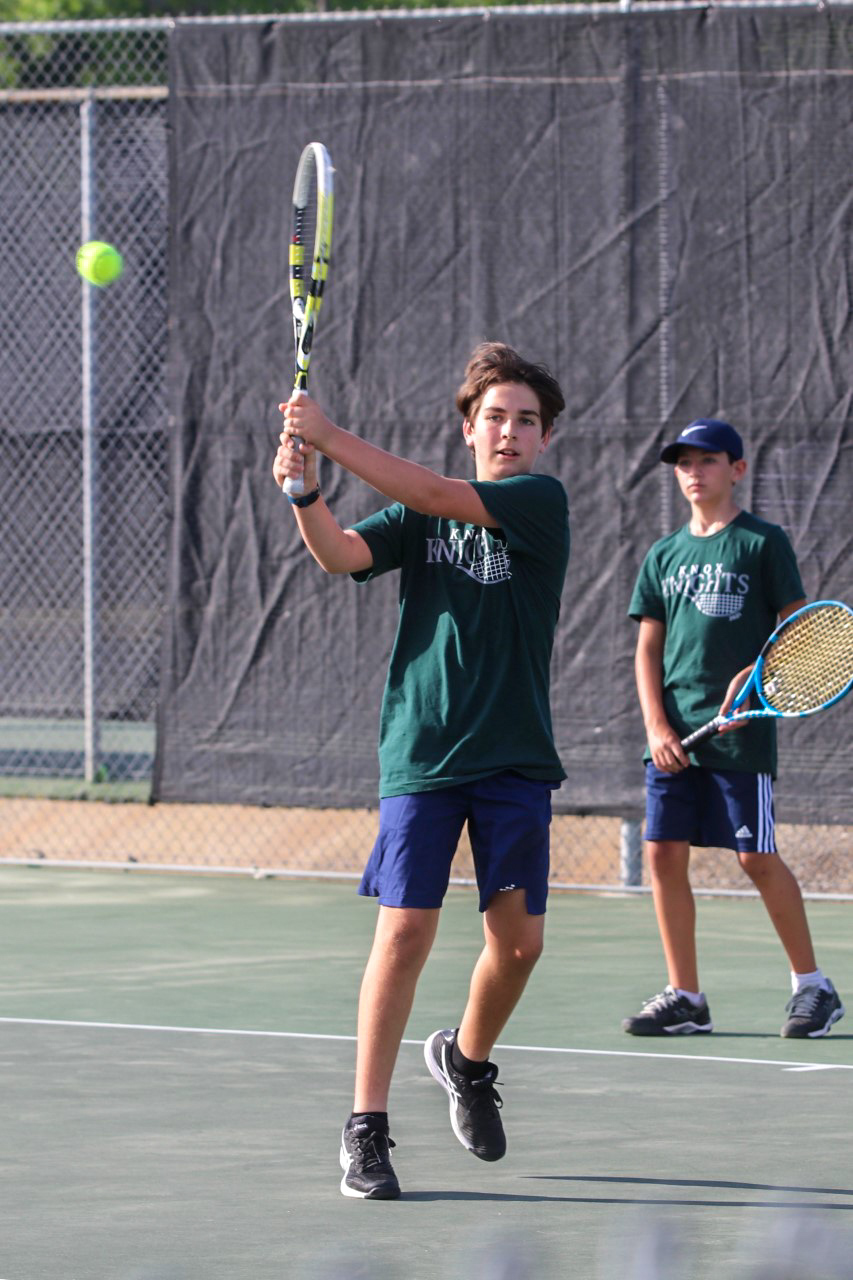 A student plays tennis at practice.